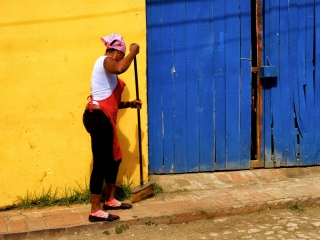 Cuban woman cleans the streets in Trinidad. Daily life in Cuba.