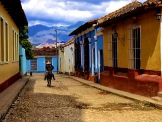 Cowboy riding down a street in Trinidad. Daily life in Cuba.