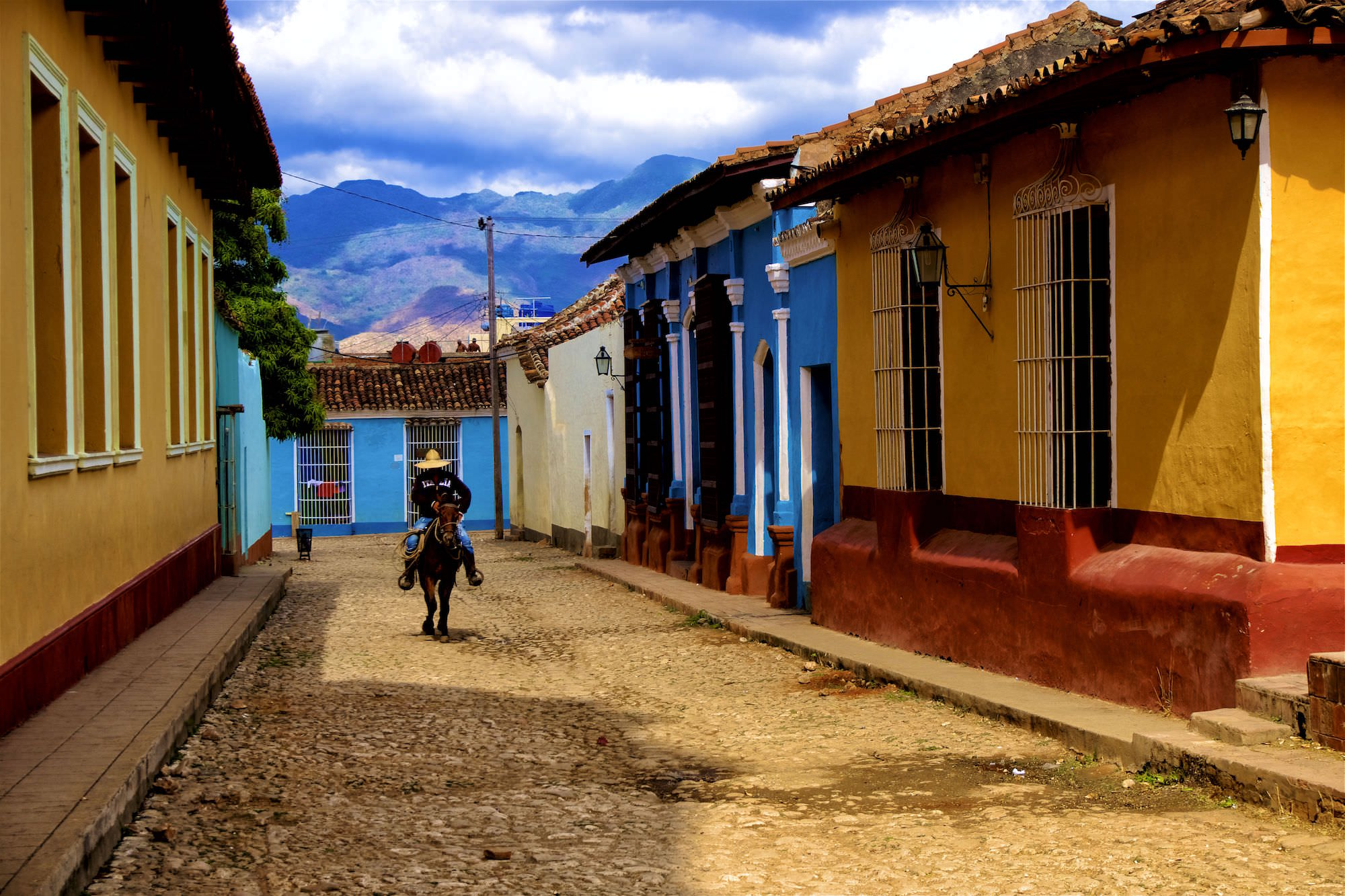 Cowboy riding down a street in Trinidad. Daily life in Cuba.