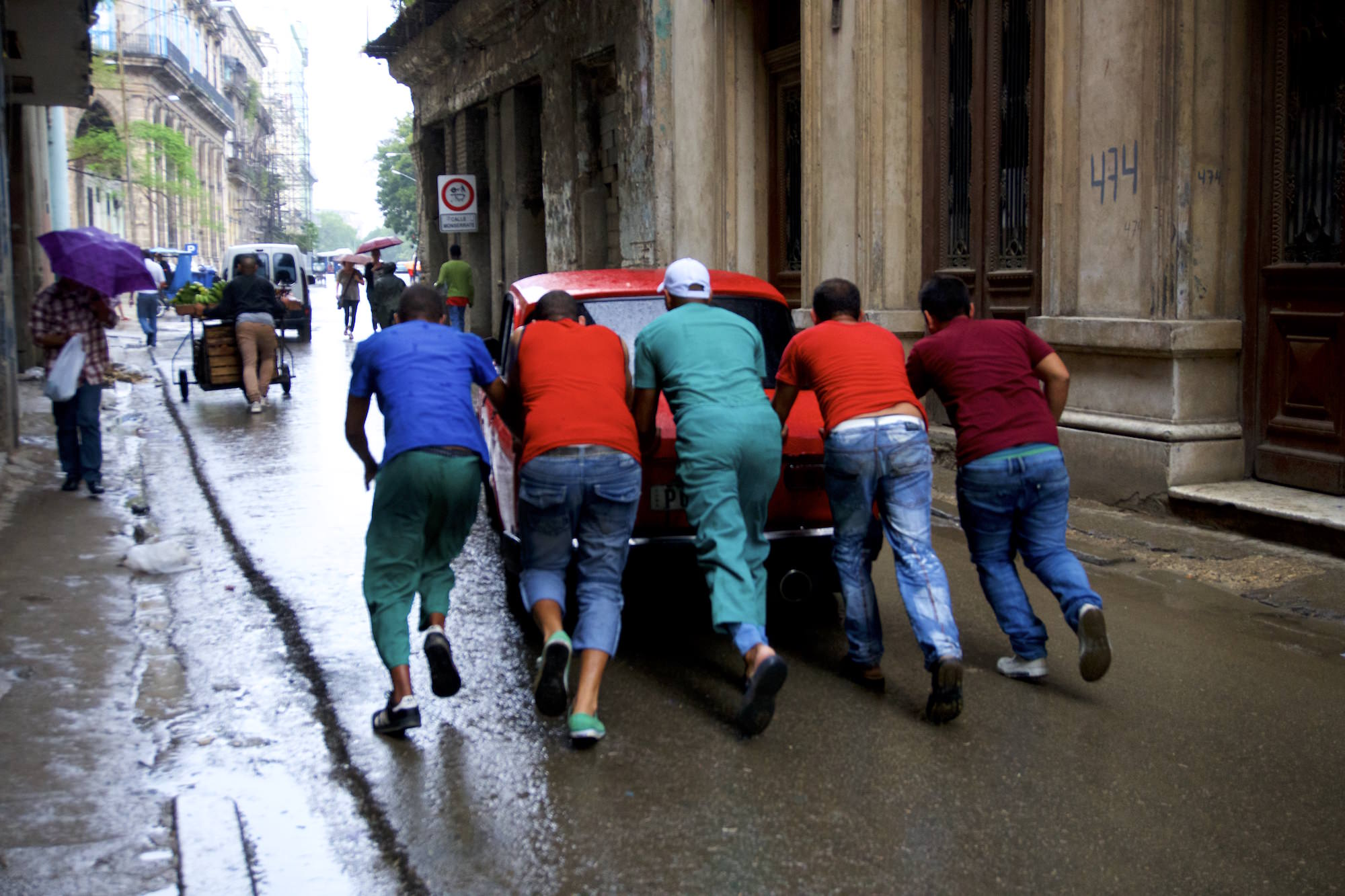 Men pushing a broken car in Havana. Daily life in Cuba.